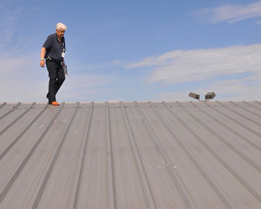 A commercial building inspector checking the roof of a large commercial property.